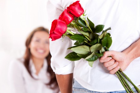 man-gives-flowers-to-woman-450x299