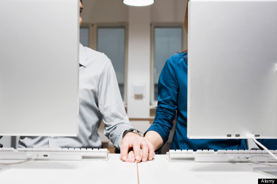 BJ0MKC young couple sitting behind computers in office holding hands